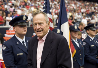 Former U.S. President George H. W. Bush smiles while wearing a pink shirt to raise breast cancer awareness in Houston