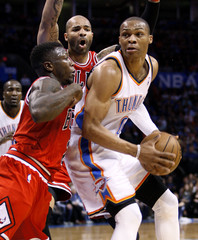 Chicago Bulls defenders Nate Robinson and Carlos Boozer guard against Oklahoma City Thunder guard Russell Westbrook in Oklahoma City