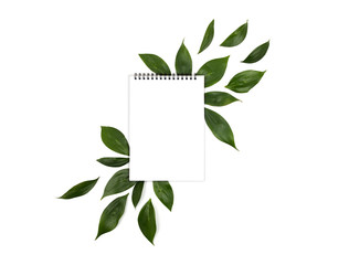White notebook isolated on a white background and green spring leaves. View from above.