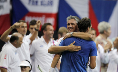 Czech Republic's Berdych is embraced by team captain Navratil after defeating Argentina's Mayer during their Davis Cup semi-final tennis match in Prague