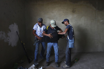 Vigilantes adjust a flak jacket in a house under construction that they use as a safe house at a periphery of Apatzingan