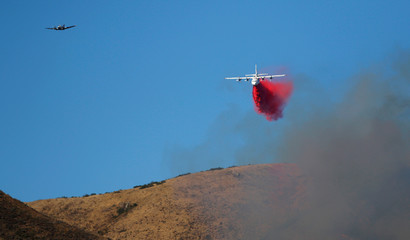 An air tanker follows a lead plane while dropping retardant over Garrapata State Park during the Soberanes Fire north of Big Sur