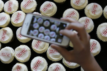 A woman takes a photograph of cupcakes at a Labour Party election event at the Royal Institute of British Architects in London