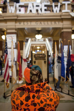 """A man takes a picture of a sign that reads """"WE ARE WI"""" as protestors fill the Capitol building in Madison"""