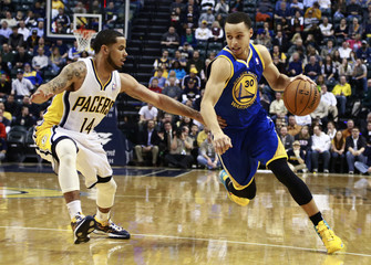 Golden State Warriors' Curry dribbles the basketball trying to get around Indiana Pacers' Augustin during an NBA basketball game in Indianapolis