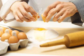 pastry dough - chef cracking egg over flour heap