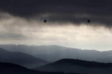 Hot air balloons fly over a forest in the Aaretal region pictureed from the Dentenberg near Bern