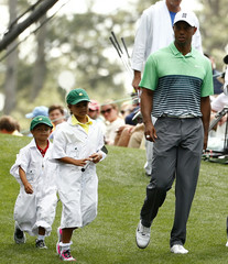 U.S. golfer Tiger Woods walks with his children Sam and and Charlie down the first fairway during the par 3 event held ahead of the 2015 Masters at Augusta National Golf Course in Augusta