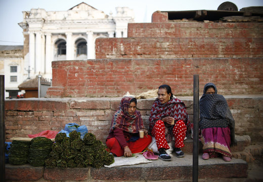 Women drink tea as they sit on the step of a temple, which collapsed during last year's earthquake, at Bashantapur Durbar Square in Kathmandu