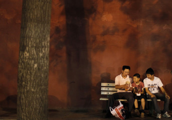 Visitors sit on a bench next to a red wall near Tiananmen Square in Beijing