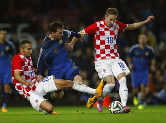 Argentina's Lionel Messi is challenged by Croatia's Marin Leovac and Marko Rog during their international friendly soccer match at Upton Park in London