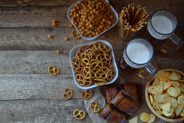 Football fan set with mugs of beer and salty snacks on wooden background. Crackers, pretzel, salted straws, nuts, dried fish. Junk food for beer or cola. Photographed with natural light