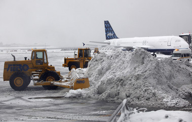 Heavy equipment is used to try to clear the tarmac as snow continues to accumulate during a 'Nor-Easter weather pattern bringing blizzard conditions to Laguardia airport, in New York