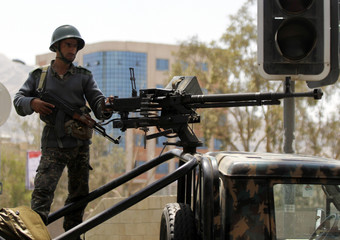 Soldier stands guard on a military vehicle at a checkpoint on a road to the city of Sanaa