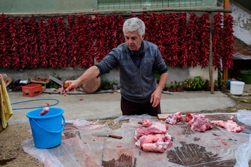 A man cuts meat as bunches of paprika hang on the wall of his house to dry in the village of Donja Lakosnica
