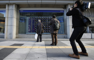 Pedestrians look at an electronic board displaying various stock prices as a cameraman records video of them outside a brokerage in Tokyo