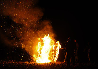 Anti-nuclear protestors set straw rolls on fire on a field in Laase near Gorleben to demonstrate against the Castor.