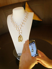 Journalist takes a photo of a rose gold necklace with a 407 carat yellow diamond during a media event in Singapore