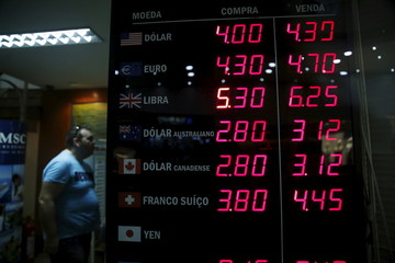 A man stands next to a board that shows the Real-U.S. dollar and several foreign currencies exchange rates in Rio de Janeiro