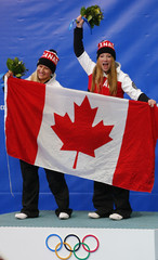 Winners Canada's pilot Humphries and Moyse pose with a national flag during the flower ceremony for the women's bobsleigh event at the 2014 Sochi Winter Olympics