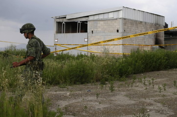 A soldier keeps watch outside a warehouse containing a tunnel, connected to the Altiplano Federal Penitentiary and used by drug lord Guzman to escape, in Almoloya de Juarez