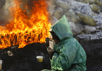 A demonstrator has a meal near a fire at a barricade erected by anti-government protesters near the site of clashes with riot police, with the air temperatures around minus 20 degrees Celsius, in Kiev