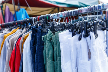 Men's and women's summer clothes sweatshirts shirts trousers jerseys coats jackets on the hanger in the shop on the street