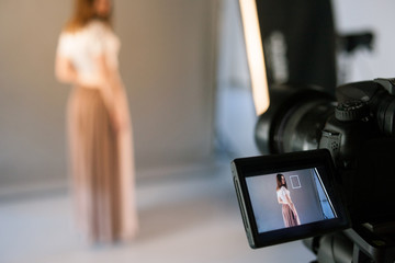 Display of camera with live view model photo. Beauty blogger shooting fashion video in studio