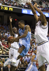 North Carolina guard Drew II passes the ball off against Georgia Tech guard Udofia and forward Favors during a college basketball game in Greensboro