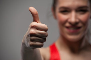 Happy sports woman showing thumbs up gesture