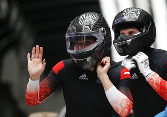 Austria's pilot Hengster and teammate Kleiser take off their helmets after completing a run in the women's bobsleigh event at the 2014 Sochi Winter Olympics