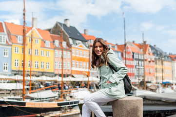 Happy young tourist woman with backpack at Copenhagen, Nyhavn, Denmark. Visiting Scandinavia, famous European destination during fall or spring. Travel and Lifestyle.