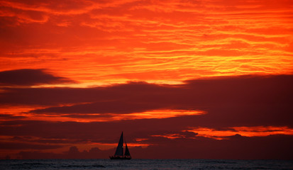 A sailboat passes in front of clouds lit up by the sunset sky off Waikiki in Hawaii, U.S.