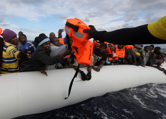 A lifeguard passes life jackets as migrants try to reach a rescue craft from their overcrowded raft, as lifeguards from the Spanish NGO Proactiva Open Arms rescue all 112 on aboard