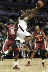 Ray Turner of Texas A&M goes to the basket past White and Gibson both of Florida State during the first half of their second round NCAA basketball game in Chicago.