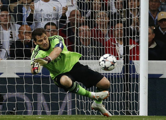 Real Madrid's Karim goalkeeper Iker Casillas saves a shot from Bayern Munich's Thomas Mueller during their Champions League semi-final first leg soccer match at Santiago Bernabeu stadium in Madrid