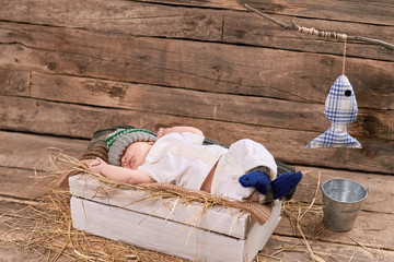 Baby fisherman is sleeping. Kid, hay and wood background. How to start fishing.