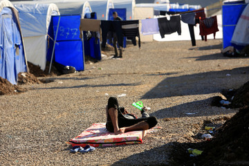 A man rests on a mattress at Hassan Sham camp for displaced people, who fled the Islamic State stronghold of Mosul, the east of Mosul
