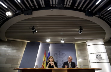 Spain's Economy Minister de Guindos gestures next to Spain's Deputy PM Saenz de Santamaria during a news conference at Moncloa Palace in Madrid
