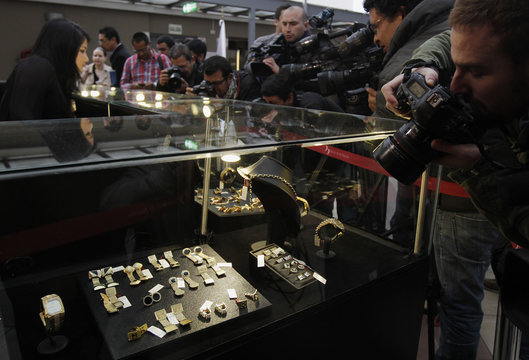 Members of the media take pictures and videos of gold watches and jewelry confiscated from Peru's former head of Intelligence Vladimiro Montesinos during a media event in Lima