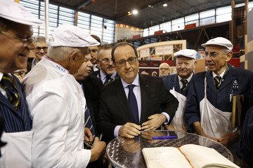 French President Francois Hollande is surrounded by butchers during his visit to the International Agricultural Show in Paris