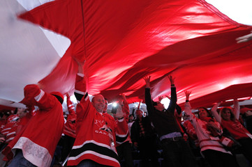 Canada fans hold up a giant flag during the first period of play in the bronze medal game of the 2012 IIHF U20 World Junior Hockey Championship in Calgary