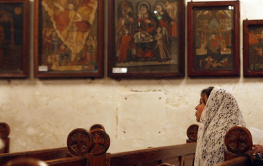 A woman attends an Orthodox Christmas mass at a Coptic church in Cairo