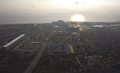 An aerial view from a helicopter shows the Adler district, with the Olympic Park under construction seen in the background, in the Black Sea resort city of Sochi