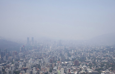 An aerial view shows Caracas among an smog cloud due to a wild forest fire at the Avila national park in Caracas