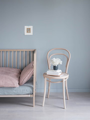 skandinavisches Kinderzimmer mit Bett und Stuhl vor grauer Wand