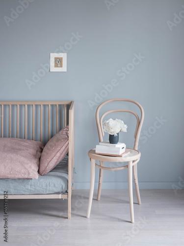 skandinavisches Kinderzimmer mit Bett und Stuhl vor grauer Wand ...