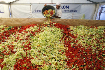 A volunteer adds vegetables to create the world's biggest vegetable salad during a Guinness World Record attempt in Pantelimon