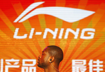 NBA Miami Heat's Wade stands in front of a company logo of Li Ning during a promotional event for Li Ning's Way of Wade sneakers, in Beijing
