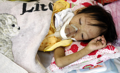 A HIV-positive girl is seen lying in a bed at the paediatric hospital in Hanoi